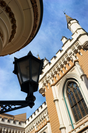 guild: Street lamp in the afternoon on a background of the ancient buildings of the Guild and the blue sky in the old town of Riga Stock Photo