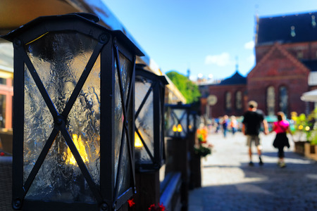 A pair of summer is on the town square past the cafe with light candles in decorative lamps Stock Photo