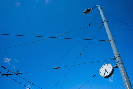 Watch the arrow at a street lamp post in the city with chaotic lines of wires on a background of blue sky
