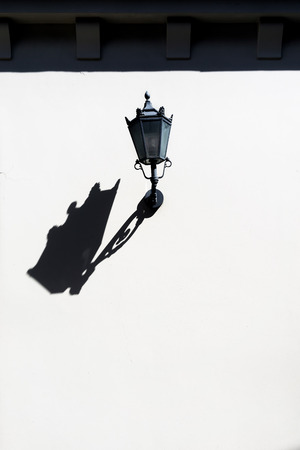 clean street: Street lamp with a long beautiful shadow on the wall of the facade clean house Riga