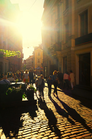 terracing: Tourists walk on the stone streets and sit on the terraces of the street restaurants, backlit in the old town of Riga