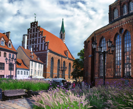 red cross red bird: Panorama Square with tourists between the churches and old traditional houses in Riga in summer