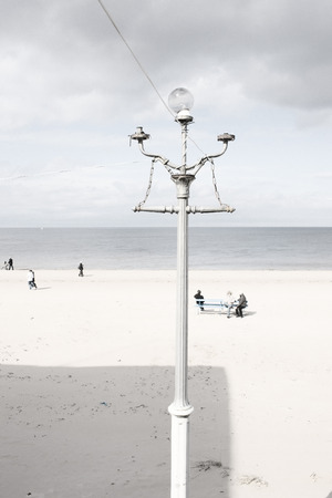 baltic people: Old broken vintage street lamp with a glass canopy on the sandy beach of the Baltic Sea with walking people in the early spring