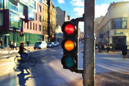 luz roja: La muchacha monta en la calle en una bicicleta entre los coches en el centro de la ciudad en una hermosa luz de un semáforo con rojo y naranja