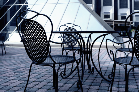 garden city: Iron chairs in summer cafe on a background of a modern building made of glass. Riga, Latvia Stock Photo