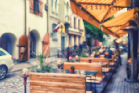 awnings: Street summer restaurant with yellow striped awnings in the historic center of Riga. Blurry