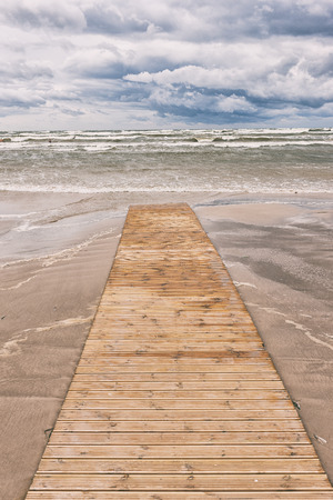 A wooden walkway on the yellow sand of the beach out to the raging sea under the beautiful clouds on the horizon