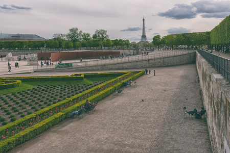 Park visitors rest in the spring in may on chairs in the Park of Paris with the Eiffel tower. Paris cityscape. France, Europe.