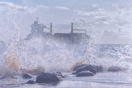 Silhouette of a commercial ship in a stormy Baltic sea through the spray of the waves on the rocks on the shore