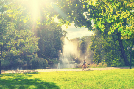 The girl on the bike in the Riga city Park among the green trees and lawn on a Sunny summer day