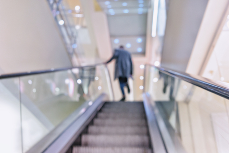 brigt: A man in a coat walks up the stairs of the escalator in the supermarket. Blurry