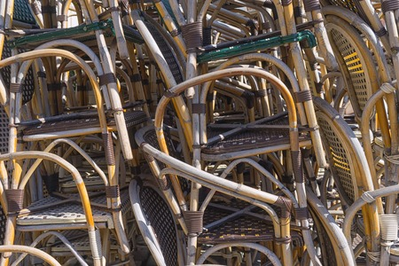 Stacked on top of each other rows of rattan chairs near a summer cafe in the early spring
