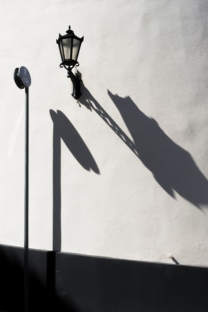 Road sign pedestrian walkway and a street lamp with a long shadow on the wall. Riga