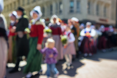 The people in the convoy with the children in national costumes on the street in celebration. Blurry