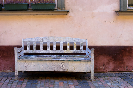 Vintage white wooden bench house at the wall of an ancient house in the centre of Riga in the spring Фото со стока