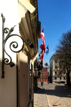 At home with national flags on the street of old Riga in the holiday by Parliament in the spring Фото со стока
