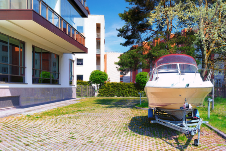 The boat is parked on the platform in a modern apartment building with large Windows on a Sunny spring day Фото со стока