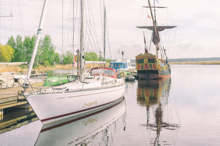 Vintage wooden sail boat moored next to the modern yacht at a mooring on the river in summer day Фото со стока