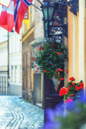 Flowers and flags on the facades of the old buildings in the historic centre of Riga. Blurry