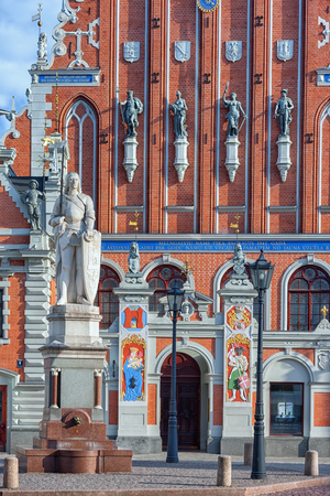 Sculpture of Roland with the sword against the facade of the House of blackheads with bas-reliefs. Riga