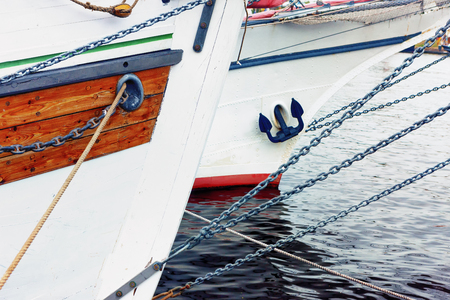 Ropes and iron chains on the nose of wooden ships with an anchor on the waves of the Bay in the port. Elements of a sailboat.