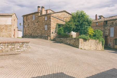 Stone square with old houses in the small classical Italian city of Tuscany
