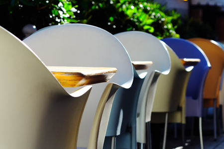 Plastic multi-colored chairs and wooden tables in a summer cafe Фото со стока