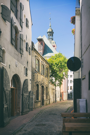 A narrow ancient street with large warehouses and green trees near the synagogue in Riga on a summer day Фото со стока