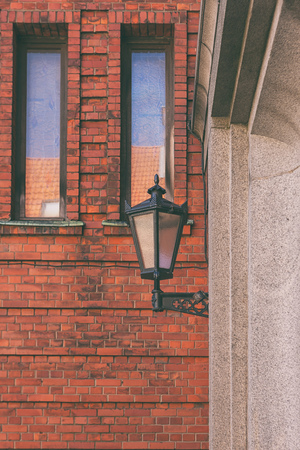 Street lamp against a red brick wall with stained glass windows. Riga