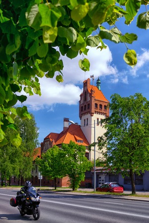Firehouse building in Riga on a background of green trees and passing by on the street biker Фото со стока