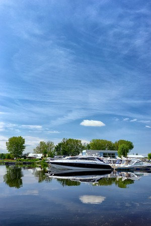 Motor yacht berthed on the river in the port of Riga on the background of green trees on summer day
