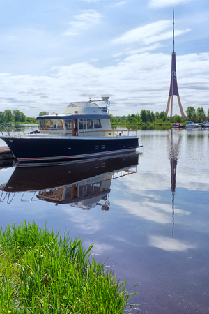 Motor yacht berthed on the river at the port in the background the television tower and the green trees in summer day