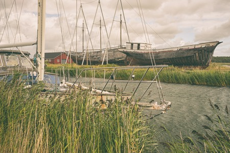 The old yacht in the Strait against the backdrop of ancient three-masted motor yacht on the Baltic sea on the island of Hiiuma