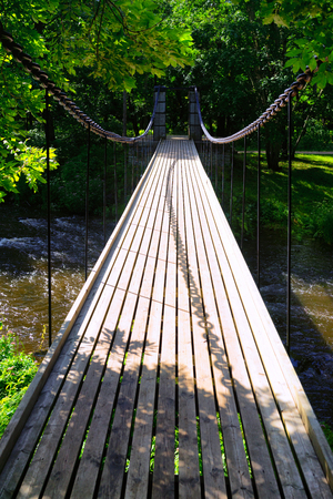 Wooden suspended bridge across the river to the green forest on metal chains with a shadow