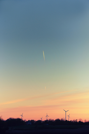 Wind generators against the background of the autumn sky with a flying airplane at sunset Stock Photo