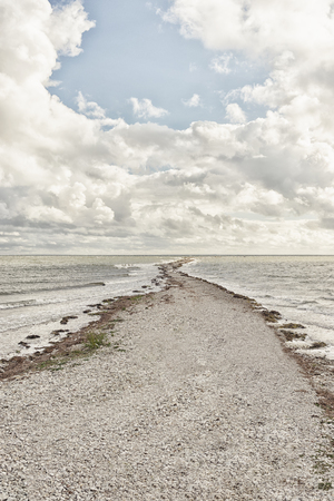 A narrow road to the horizon of stones in the middle of the Baltic Sea on a sunny day with beautiful clouds. Estonia. Hiiuma, Kassari. Saare tirp Stock Photo