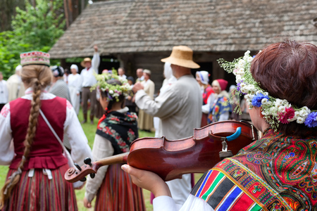 People in Latvian national costumes are dancing on the street in the countryside in summer Stock Photo