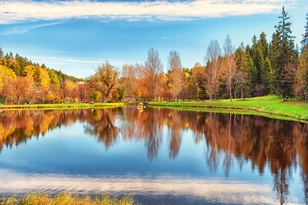 Autumn forest is reflected in the lake Ligatne National Park in Latvia on a sunny day