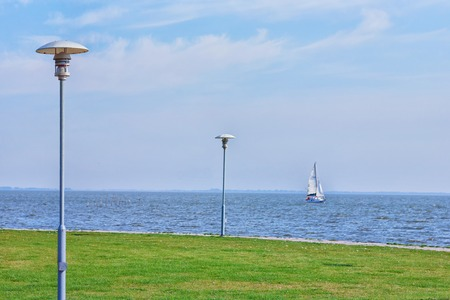 A sailing yacht runs along the shore with a green lawn and slender lanterns. Neringa Stock Photo