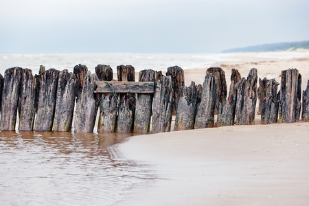 The remains of an old wooden pier on the sandy beach of the Baltic Sea