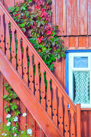 A graceful wooden carved staircase by the window with a curtain against a background of flowers and flowering ivy in the summer Stock Photo