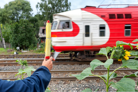 The train is passing by the railway worker with a flag. Latvia Stock Photo