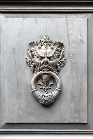 A bas-relief with a ring in his mouth on the painted black doors of a house in Italy