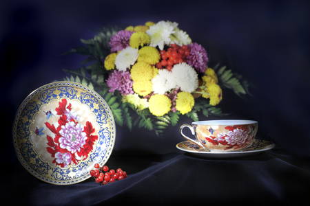 Tea set from mugs and saucers against a bouquet of flowers and berries Stock Photo