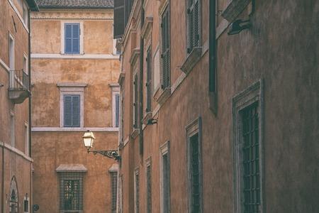 Уличный фонарь на стене старого дома на фоне фасадов с окнами в Риме Фото со стока