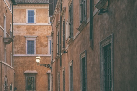 Street lamp on the wall of an old house against the backdrop of facades with windows in the city of Rome Stock Photo