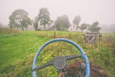 Дома в сельской местности на фоне синего рулевого колеса от автомобиля и тумана ранним утром