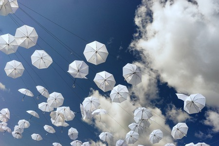 White umbrellas against a blue summer sky with clouds