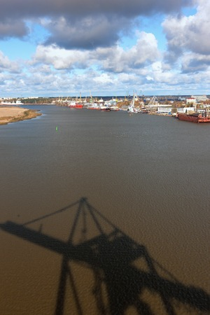 Port with cranes on the Daugava River in Riga, the capital of Latvia, with a shadow on the water with waves of a crane for the loading of Containers Фото со стока