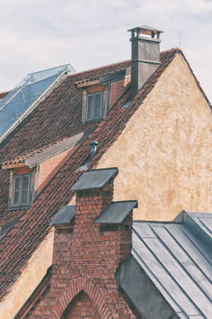 Red tiled roof on pointed houses with chimneys of the old city of Riga Фото со стока